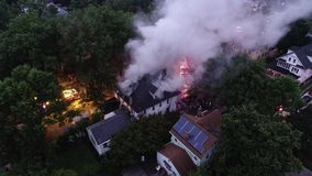 Aerial view of fire trucks and apparatus battling a house fire.  stock video footage