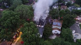 Aerial view of fire trucks and apparatus battling a house fire.  stock footage