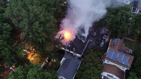 Aerial view of fire trucks and apparatus battling a house fire.  stock video