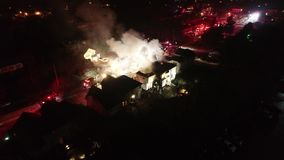Aerial view of fire trucks and apparatus on scene of house fire stock video