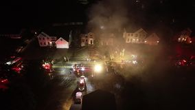 Aerial view of fire trucks and apparatus on scene of house fire stock footage