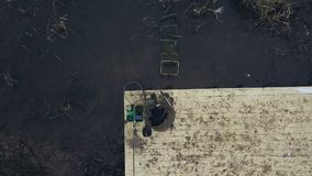Aerial view fisherman sitting on river pier with fishing rod waiting bite. Aerial view fisherman sitting on chair at river pier with fishing rod waiting for bite stock footage