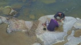 Aerial View Fishermen Let out Fish Put into Bag Sitting on Rocks stock video