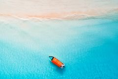 Aerial view of the fishing boats in clear blue water. At sunny day in summer. Top view from drone of boat, sandy beach. Indian ocean in Zanzibar, Africa royalty free stock photography