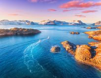 Aerial view of fishing boats, rocks in the blue sea. Snowy mountains and colorful purple sky with red clouds at sunset in winter in Lofoten islands, Norway stock image