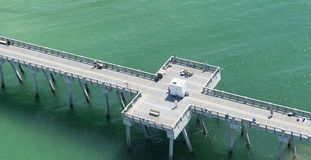 An aerial view of a fishing pier in Panama City Beach,Florida in the waters of the emerald green Gulf of Mexico. An aerial view of a fishing pier in Panama City Stock Image