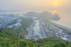 Aerial view of a fishing village at dawn on northern coast of Taipei Taiwan. ! Aerial view of a harbor in the foggy morning in northern Taiwan royalty free stock photo
