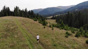 Aerial view of fit man running in mountains forest on weekend, amazing trail running moments, achieving fitness goals