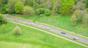 Aerial view of five cars driving in a countryside road. Among green fileds Stock Images