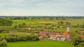 Flemish countryside with fields with trees, old houses and a windmill Stock Images