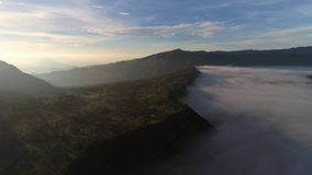 Aerial view flight over Cemoro Lawang, small village in morning mist. stock video