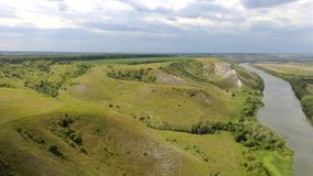 Aerial View. Flight over a green grassy rocky hills with river valley. Aerial View. Flight over a green grassy rocky chalk hills with river valley, cloudy sky stock video footage