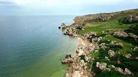 Aerial view: flight over the сoast of thousands bays on General beach with shells and rocks near Kerch, Crimea.