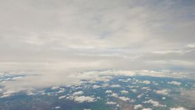 Aerial view fly above clouds. airplane window view blue sky down to land. fluffy clouds in ozone level. atmosphere in cloudy sky