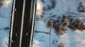 Aerial view: Flying above the park covered with snow during sunset. On cold winter day. Scenic panorama stock footage