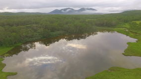Aerial View. Flying across the lake to the copter. The lake reflecting forest and clouds stock video
