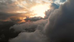 Aerial view flying through cumulus thunderclouds at sunset. Gold colored sunset cloudiness in high contrast. Real sky