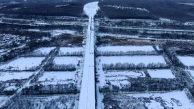 Aerial view flying a drone over a snowy high-speed road and bridge over the river at high altitude. Beautiful panoramic landscape stock video