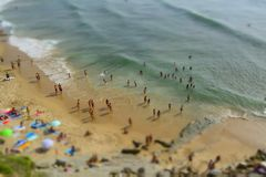 Aerial View From Flying Drone Of People Crowd Relaxing On Beach In Portugal. People bathing in the sun, swiming and playing games on the beach. Tourists on the stock image