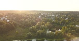 Aerial View. Flying over the beautiful sunny village and lake. Aerial View. Flying over the beautiful sunny forest trees, lake and forest. Aerial camera shot stock video footage