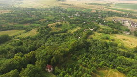 Aerial View: Flying over the forests and houses in 4k.  stock footage
