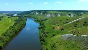 Aerial view of flying over green grassy rocky chalk hills, mountains and a river. Don in Voronezh region, Russia. Drone flight at nature stock video footage