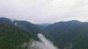 Aerial view. Flying over the high mountains in beautiful clouds . Aerial camera shot. stock video
