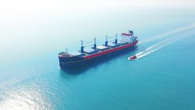 AERIAL VIEW: Flying over massive ship filled moving in the quiet sea. Cargo being moved by large international cargo. Ship to final destination stock video