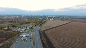 Aerial View. Flying over the road, field and beautiful autumn trees. Landscape panorama. Aerial camera shot. stock video footage