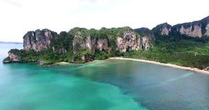 Aerial view flying over Thai island towards beautiful green mountains and white sandy beach. Krabi island, Thailand