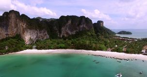 Aerial view flying over Thai island towards beautiful green mountains and white sandy beach. Krabi island, Thailand stock footage