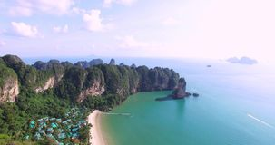 Aerial view flying over Thai island towards beautiful green mountains and white sandy beach. Krabi island, Thailand stock video footage