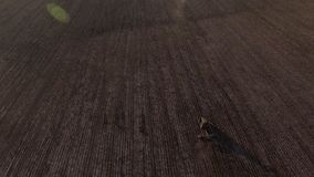 Aerial view flying over the top of a combine harvester and tractor in a field stock footage