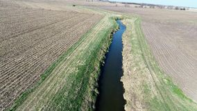 Aerial view flyover Illinois farmland in early spring with creek and open fields Royalty Free Stock Images