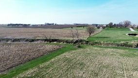 Aerial view flyover Illinois farmland in early spring with creek open fields and country houses Royalty Free Stock Image
