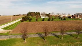 Aerial view flyover Illinois farmland in early spring with creek open fields and country houses stock footage