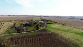 Aerial view flyover Illinois farmland in early spring with creek open fields and country houses Stock Photo