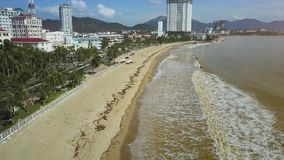 Waves Roll on Ocean Beach after Typhoon in Resort Town. Aerial view foamy waves roll on sand beach along ocean drive with traffic after powerful typhoon in stock video footage