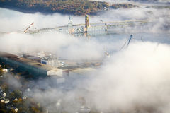 Aerial view of fog over Bath Iron Works and Kennebec River in Maine.  Bath Iron Works is a leader in surface combatant design and  Royalty Free Stock Photo