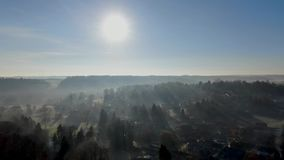 Aerial view of countryside landscape with forests and farmlands during morning foggy day stock footage