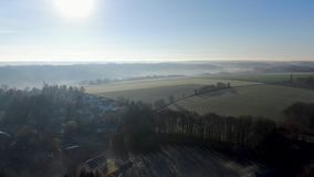 Aerial view of countryside landscape with forests and farmlands during morning foggy day stock video