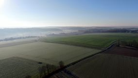 Aerial view of countryside landscape with forests and farmlands during morning foggy day stock video footage