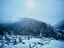 Aerial view of foggy countryside and houses in snowy valley. Hills and mountains with pine tree forest covered in snow royalty free stock photography