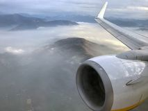 Aerial view on fogy mountains from airplane.  stock photo