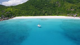 Aerial view footage of luxury catamaran yacht moored in clear turquoise blue ocean water of Petite Anse sandy beach of. La Digue island, Seychelles. Travel stock video footage