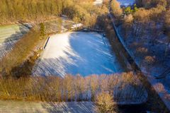 Aerial view of a football field of a district league team in a village with the first snow of the year. Drone shot stock photo