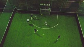 Aerial view of football pitch at night with amateur football players playing the game in the city. Clip. Top view of the stock photography