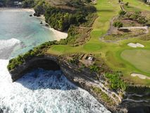 Aerial view of luxury golf course next the cliff, ocean and beach in Bali island, Indonesia. royalty free stock photos