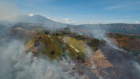 Aerial view Forest fire. Jawa island, Indonesia. Aerial view forest fire on the slopes of hills and mountains. Forest and tropical jungle deforestation for Stock Photos