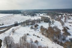 Aerial view of forest river in winter day. Winter snowy landscape with river, forest and meadow Stock Photography